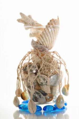Sea cockleshells and stones in a vase with a grid Stock Photo