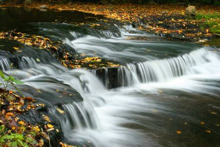 Autumn waterfall on the river, with leaves, in Estonia