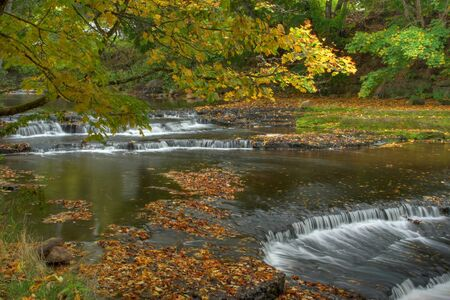 Autumn waterfall on the river, with leaves, in Estonia photo