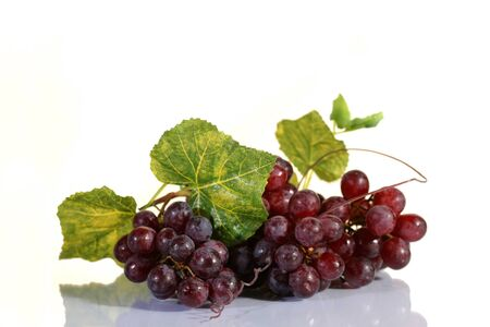 Grape cluster with leaves on a white background