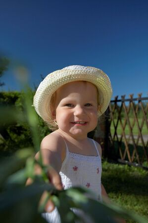 Cutel little girl in hat on a summer day
