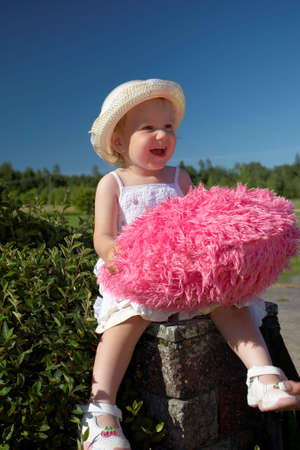 Cutel little girl in hat with pink toy on a summer day