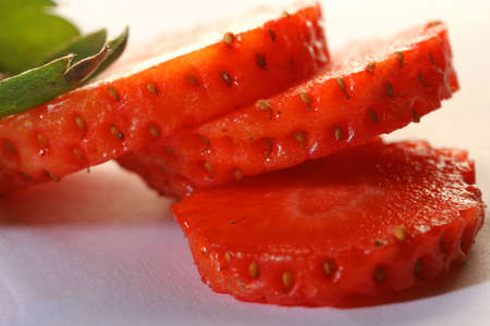 Segments of ripe cut strawberry with leaves