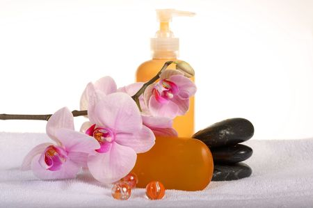 Spa treatment: orchid, cream and stones on towel