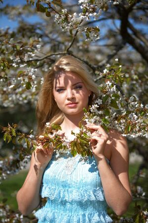 Beautiful girl near blossoming tree photo