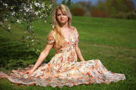 beautiful girl sitting near blossoming tree Stock Photo