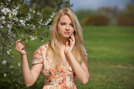 beautiful girl near blossoming tree photo