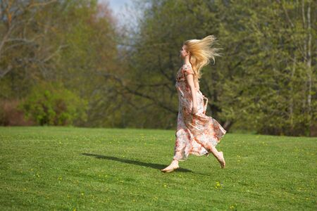 Happy beautiful young woman jumping (running) on meadow photo