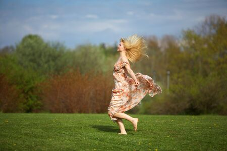 Happy beautiful young woman jumping (running) on meadow