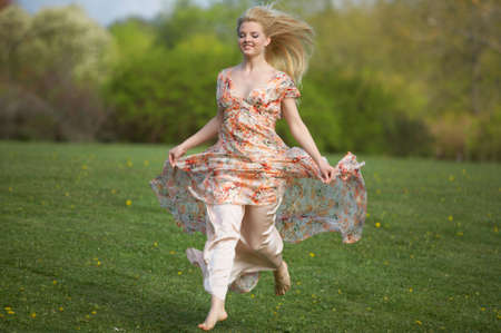 Happy beautiful young woman jumping (running) on meadow Stock Photo - 4924975