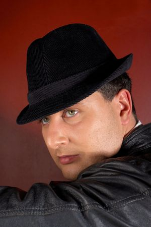 Close-up of a young man in a trilby looking over shoulder photo