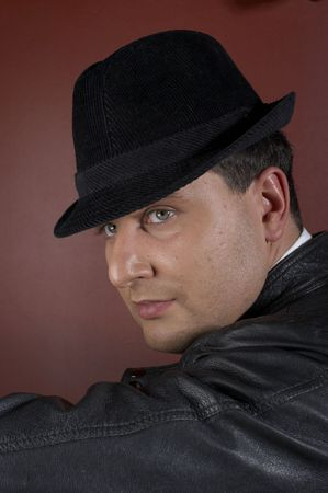 Close-up of a young man in a trilby looking over shoulder Stock Photo