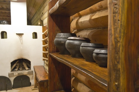 yesterday: Interior of Russian log hut with the furnace and pots Stock Photo