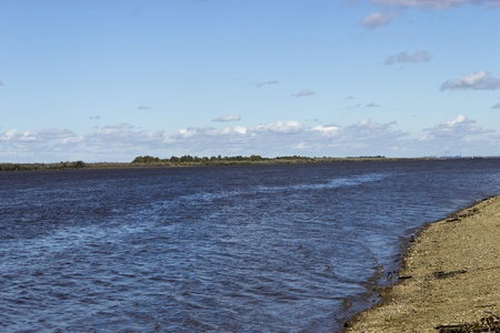 The river flowing afar along sandy coast photo