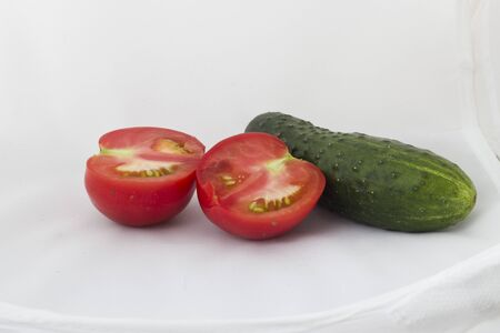 The cut tomato and cucumber on a white background photo