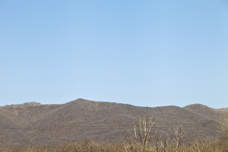 Hills in the distance in the early spring against the blue sky photo