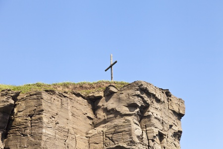 The cross on the rock over the sea meets floating ships photo