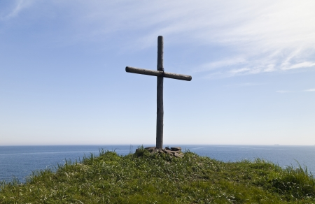 religious: The cross on the rock over the sea meets floating ships