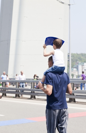 People celebrate city birthday, dance and walk on the bridge with children and tags