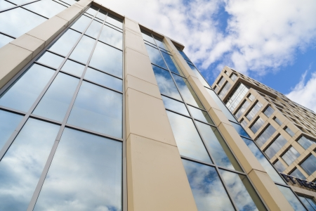 In windows of the modern building are reflected the blue sky and clouds Standard-Bild