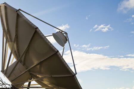 The parabolic antenna against the blue sky accepts a signal photo
