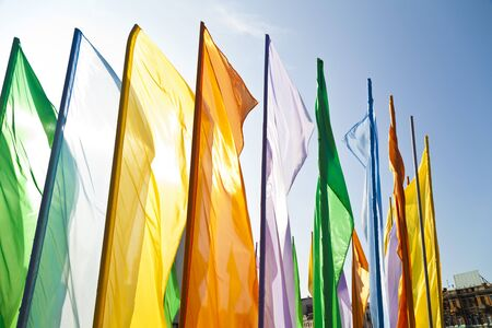 Multi-colored flags in the light of a bright sun against the blue sky photo