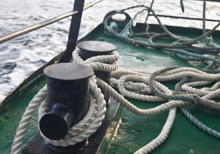 bollards: Bollards by the ship, tied with ropes, during ship movement