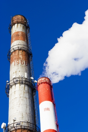 coal fired: Pipes of power plant smoke against the bright blue sky