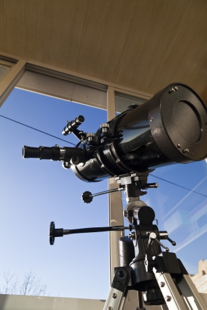 The telescope looks out of the window waiting for stars photo