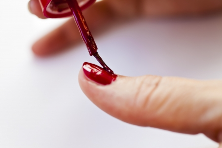 The girl makes up nails with a red varnish photo