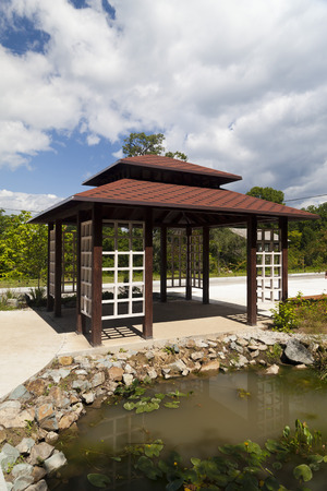 japanese tea garden: Japanese arbor on the bank of a small pond in the wood