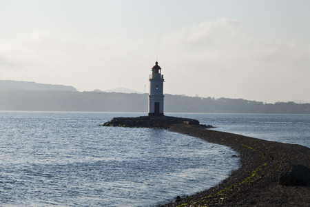 andros: Lighthouse on the shore of the open sea in front of the harbor