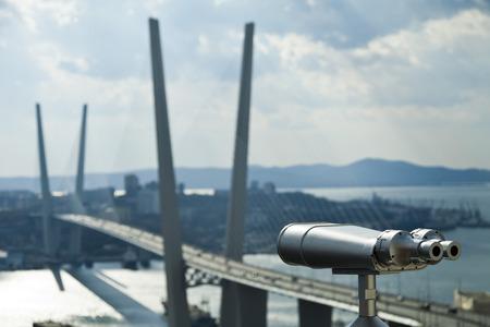 The tourist telescope looks at the sea and a big suspension bridge Standard-Bild