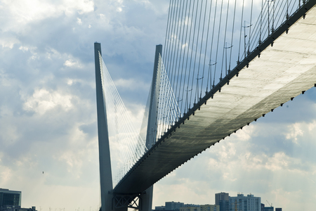 Big suspension bridge in the light of the bright midday sun and against black clouds