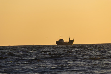 The ships in the evening sea in beams of the setting sun photo