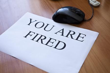"""Inscriptie """"U bent ontslagen"""" op het vel wit papier"""