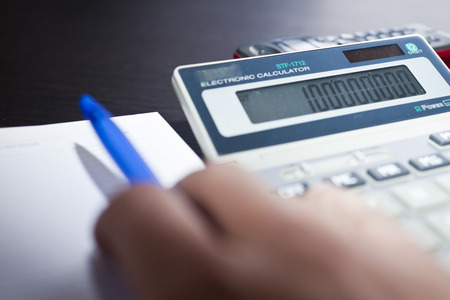 Table at office with papers, the calculator and a stationery photo
