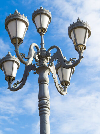 Streetlight against the blue sky with white clouds photo