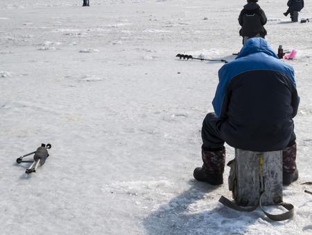 Winter fishing on ice of the frozen sea gulf photo