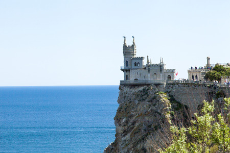 The castle by the sea is on the rock highly above water photo