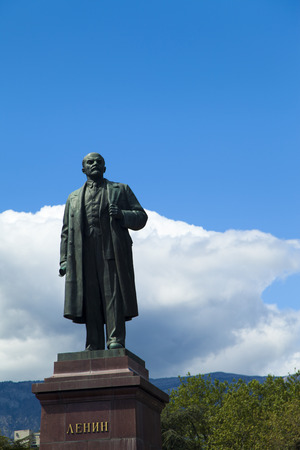 The monument to Lenin is among palm trees and against the bright blue sky photo