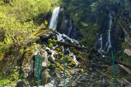 cascade mountains: The falls in mountains flow from above and rustle Stock Photo