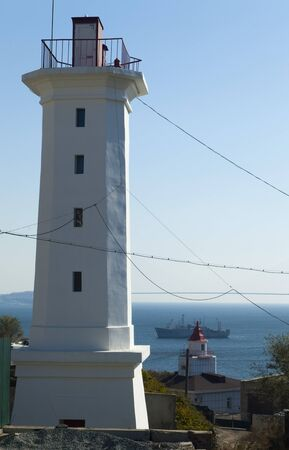 helps: Lighthouse on the coast helps ships at sea