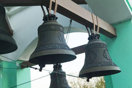Bells on a belfry waiting for evening service and the bell ringer