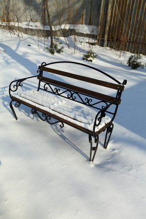 waits: The bench in snow costs, forgotten by all and waits for spring