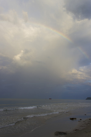 The rainbow over the sea has appeared after a rain and has decorated with itself gloomy morning