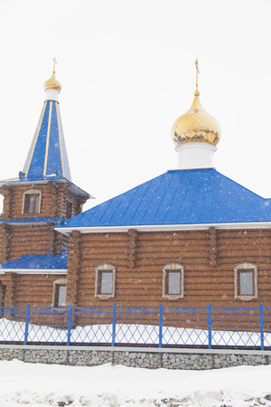 The wooden orthodox church costs under snow among snow open spaces 免版税图像 - 102174942