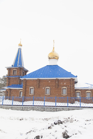 The wooden orthodox church costs under snow among snow open spaces
