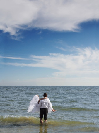 Couples going into the sea photo
