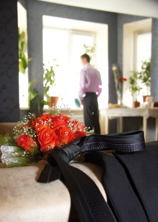 Bouquet and tie, against the background of the groom waiting for the wedding Stock Photo